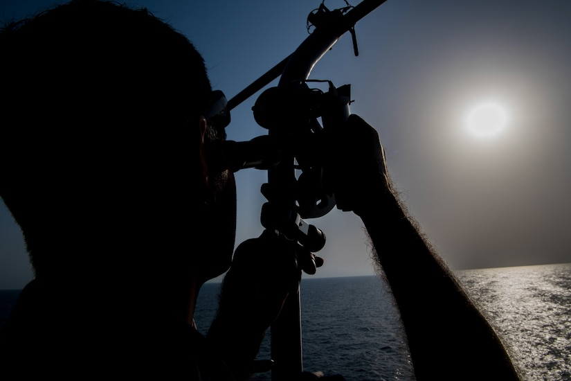 Sailor uses navigational sextant.
