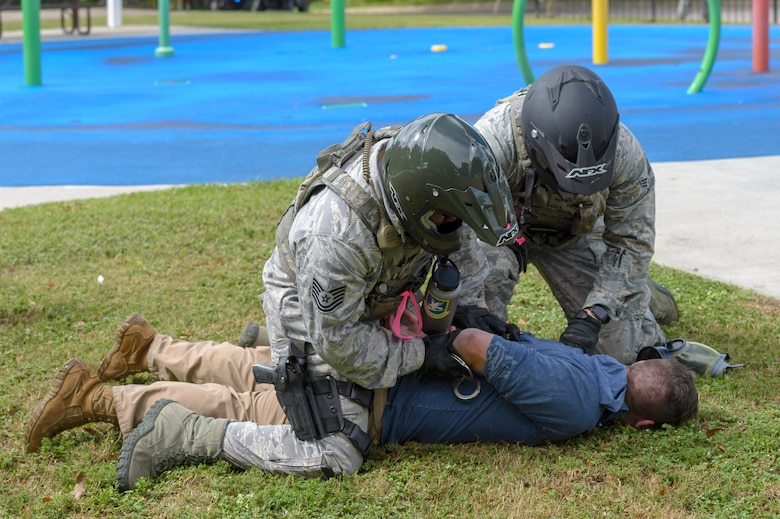 Members of the 81st Security Forces Squadron apprehend a terrorist role player during the Anti-Terrorism, Force Protection Condition and Chemical, Biological, Radiological, Nuclear and high-yield Explosives training exercise at the Marina at Keesler Air Force Base, Mississippi, Oct. 17, 2018. The AT/FPCON/CBRNE exercise was conducted to evaluate the mission readiness and security of Keesler. (U.S. Air Force photo by Andre' Askew)