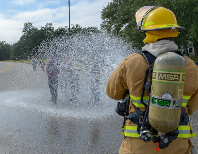 "A Keesler firefighter guides ""victims"" through a gross decontamination site during the Anti-Terrorism, Force Protection Condition and Chemical, Biological, Radiological, Nuclear and high-yield Explosives training exercise at the Marina at Keesler Air Force Base, Mississippi, Oct. 17, 2018. The AT/FPCON/CBRNE exercise was conducted to evaluate the mission readiness and security of Keesler. (U.S. Air Force photo by Andre' Askew)"