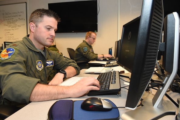 Two U.S. Air Force Airmen log into computers using keyboards inside an Air Operations Weapon System Suite at Joint Base McGuire-Dix-Lakehurst, October 12.
