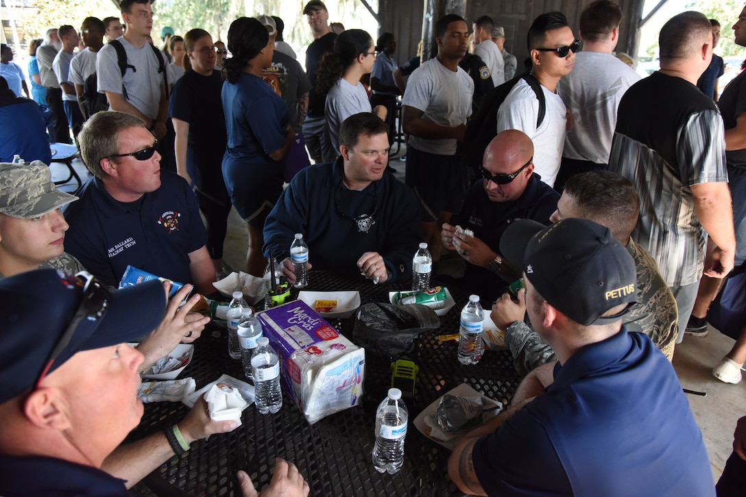 Members of the Keesler Fire Department eat lunch during Wingman Day at the Marina on Keesler Air Force Base, Mississippi, Oct. 18, 2018. Wingman Day focused on the physical domain, resiliency and team-building initiatives across the base followed by a barbeque and games at the Marina. (U.S. Air Force photo by Kemberly Groue)