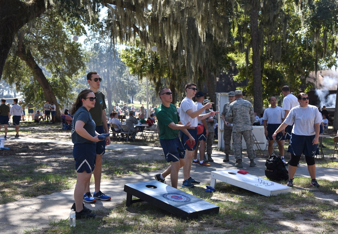 Keesler Airmen participate in a game of corn hole during Wingman Day at the Marina on Keesler Air Force Base, Mississippi, Oct. 18, 2018. Wingman Day focused on the physical domain, resiliency and team-building initiatives across the base followed by a barbeque and games at the Marina. (U.S. Air Force photo by Kemberly Groue)