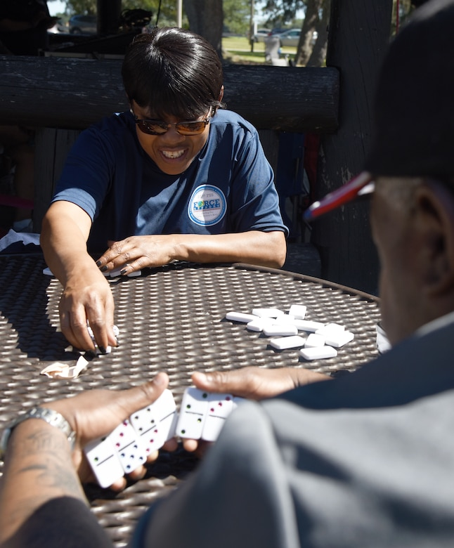 Dee Keyes, 81st Force Support Squadron secretary, and Louis Bridges, 81st FSS education specialist, play a game of dominos during Wingman Day at the Marina on Keesler Air Force Base, Mississippi, Oct. 18, 2018. Wingman Day focused on the physical domain, resiliency and team-building initiatives across the base followed by a barbeque and games at the Marina. (U.S. Air Force photo by Kemberly Groue)