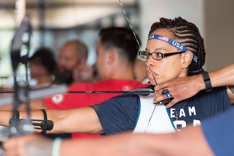 An archer pulls an arrow back in her bow and aims with one eye closed.