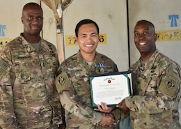 Command Sergeant Major Nathaniel Atkinson joins John S. Solomon as he receives his NATO and Commander's Award for Civilian Service from Afghanistan District Commander, Jason Kelly.