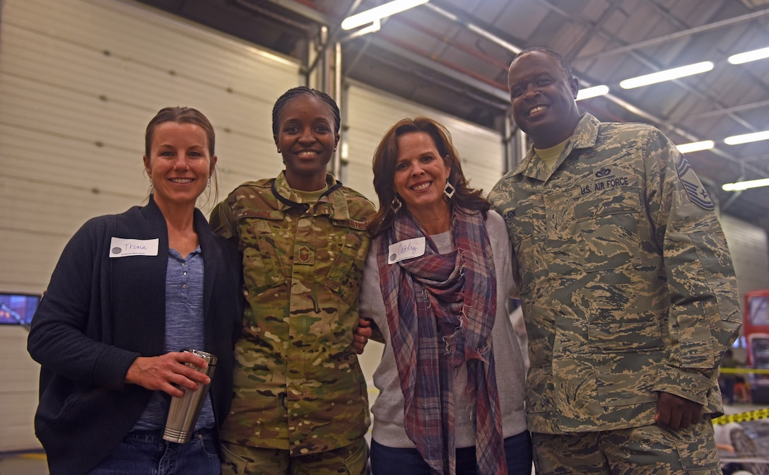Trina Bentley, wife of 100th Air Refueling Wing Vice Commander Cassius Bentley, U.S. Air Force Senior Master Sgt. Afryea Clark, 352nd Special Operations Wing Exercise Superintendent, Cathy Amrhein, wife of 100th ARW Commander Christopher Amrhein, and U.S. Air Force Chief Master Sgt. Daniel Clark, 100th Civil Engineering Squadron chief enlisted manager, pose for a photo during a Hearts Apart event Oct. 18, 2018, on RAF Mildenhall, England. The 100th Civil Engineering Squadron hosted the monthly event, which helps brings Team Mildenhall families of deployed Airmen closer during times of separation. (U.S. Air Force photo by Airman 1st Class Brandon Esau)