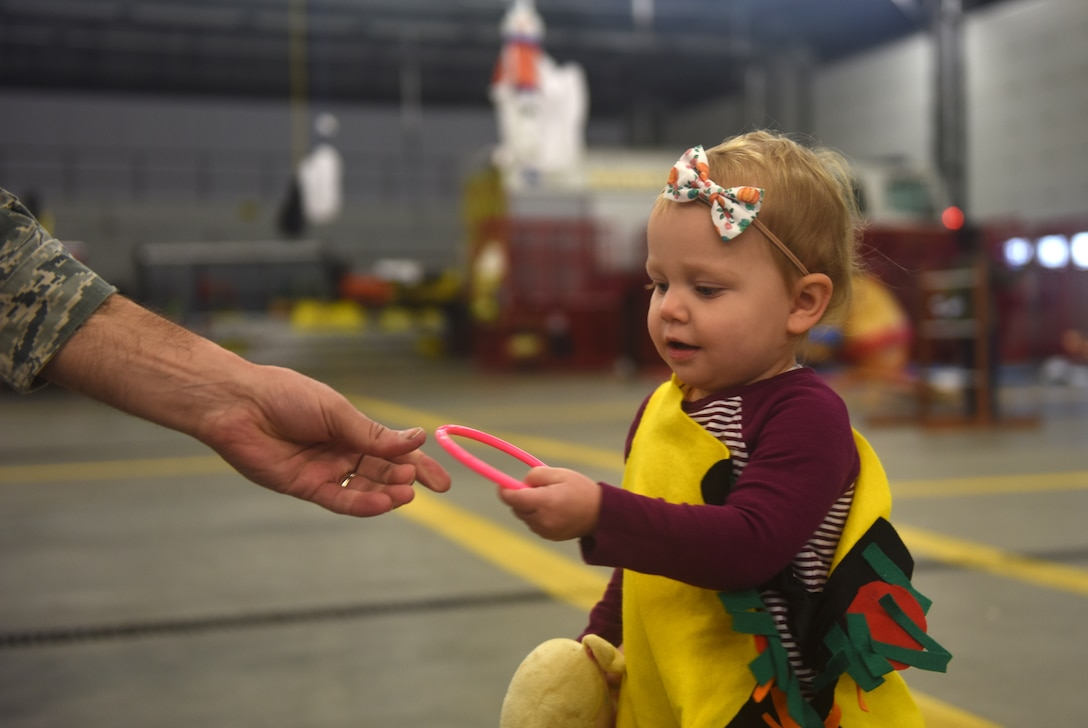 The daughter of a deployed Team Mildenhall Airman takes hold of a ring from U.S. Air Force Lt. Col. Joshua Lundeby, 100th Operations Support Squadron commander, during a Halloween-themed Hearts Apart event Oct. 18, 2018, on RAF Mildenhall, England. The event was hosted by the 100th Civil Engineering Squadron along with the Mildenhall Key Spouses' Club. The families enjoyed food, games and a costume contest. (U.S. Air Force photo by Airman 1st Class Brandon Esau)