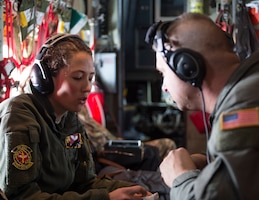 U.S. Air Force Tech. Sgt. Anne Oberg left, gives symptoms of being sick to Senior Airman Joshua Ewert, both members of the 109th Aeromedical Evacuation Squadron, during a training flight in Minn., Oct. 9, 2018