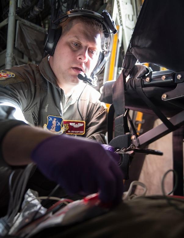 U.S. Air Force Senior Airman Joshua Ewert, 109th Aeromedical Evacuation Squadron, simulates placing a defibrillator monitor onto a role-player during a training flight in Minn., Oct. 9, 2018.