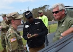 Captain Sha-Raya Bates, commander of the Washington, Ga.-based 214th Forward Support Company discusses operations at a point of distribution in Seminole County with County Commissioner Darius Culverson. The 1214th has supported relief operations in hurricane impacted counties in Ga. since mobilizing October 11.