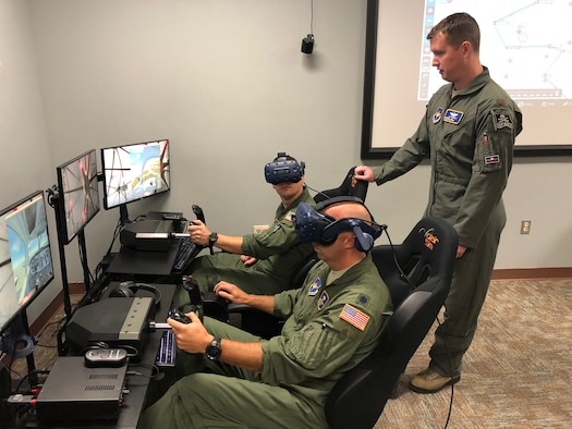 Lt. Col. Derek McCafferty (left) and Maj. Erik Jones, 99th Flying Training Squadron instructor pilots, prepare for a virtual flying training sortie Oct. 9, 2018, at Joint Base San Antonio-Randolph, Texas.  The 99th FTS, along with the 560th FTS, have integrated virtual reality simulators into the  pilot instructor training syllabus as part of an overall strategic effort to leverage emerging technology across the training enterprise.