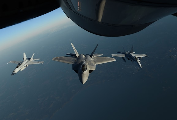 A U.S. Air Force F-22 Raptor and two Finnish air force F/A-18 Hornets fly behind a U.S. Air Force KC-135 Stratotanker during training off the coast of Finland, Oct 19, 2018. The Raptors trained with different NATO allies and partners to deter any potential threats and increase regional security. (U.S. Air Force photo by Senior Airman Luke Milano)