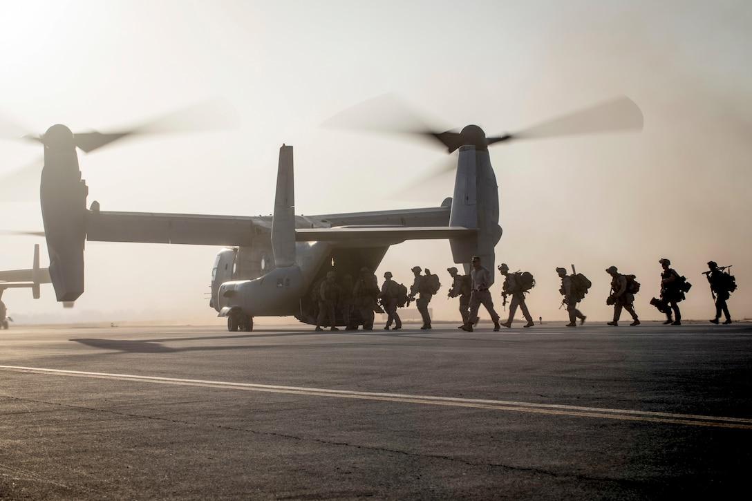 Marines board an Osprey in a line.