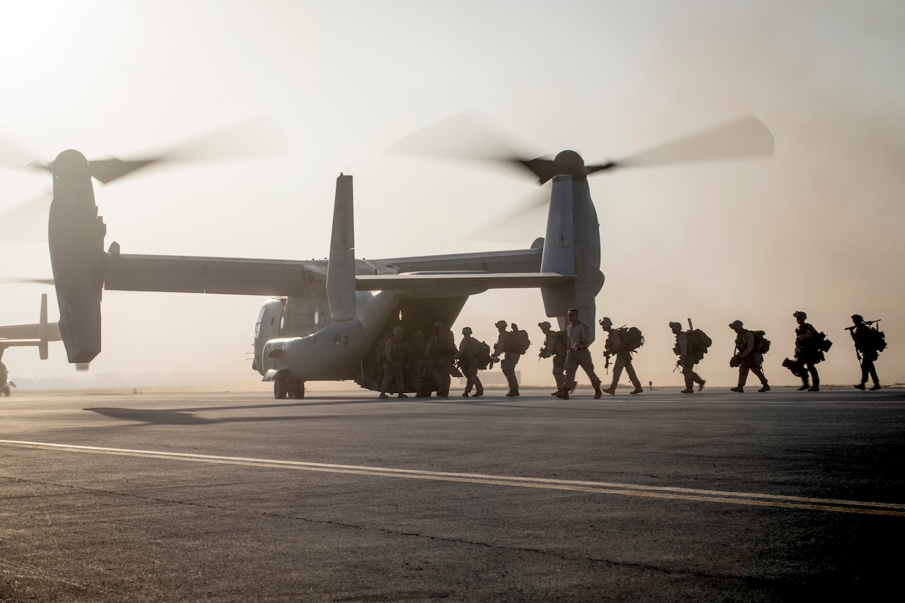 Marines board an Osprey in a line.
