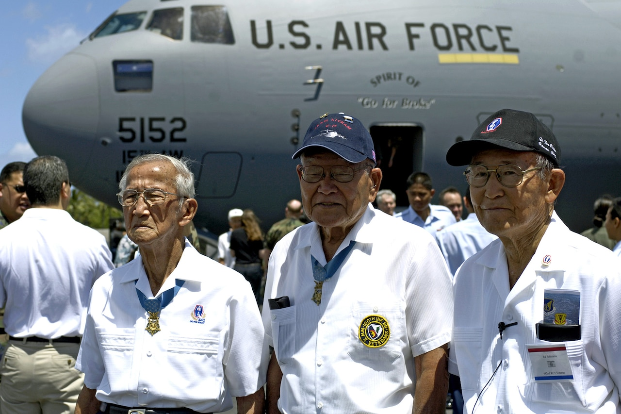 Three World War II veterans stand in front of Air Force cargo plane