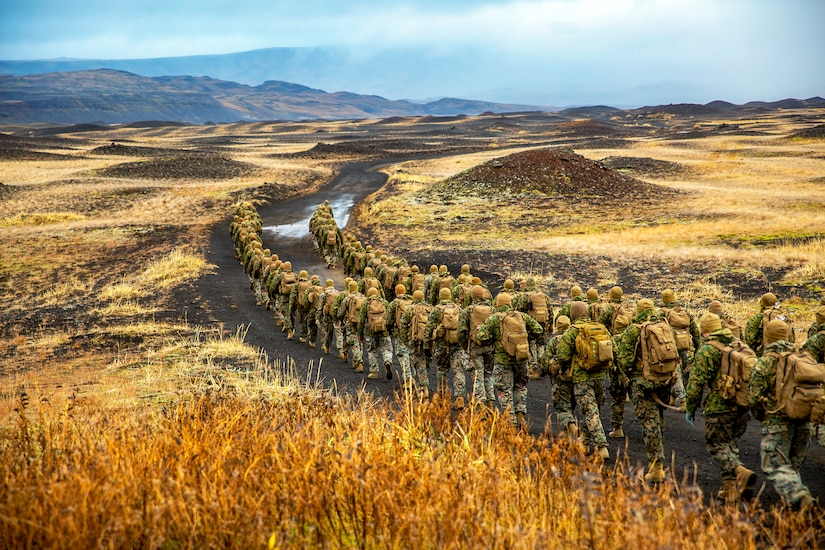 Marines hike across the flat landscape of Iceland as mountains loom in the distance.