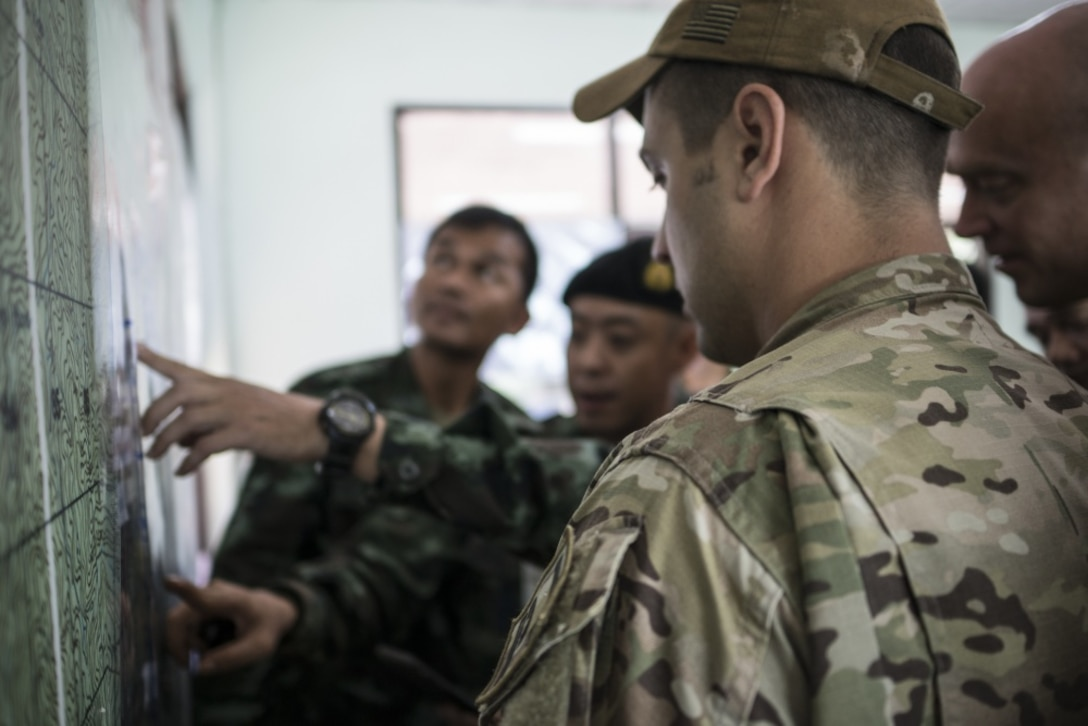 Airmen from the U.S. Indo-Pacific Command (USINDOPACOM) examine a map with Royal Thai military officials June 29, 2018, at Chiang Rai, Thailand. The United States, through USINDOPACOM, sent a search and rescue team to Tham Luang cave in Northern Thailand at the request of the Royal Thai government to assist in the rescue of the missing Thai soccer players and their coach. (U.S. Air Force photo by Capt. Jessica Tait)