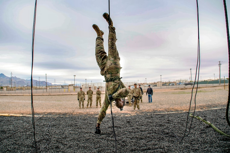 An air assault instructor reaches out to touch the ground beneath his head while hanging upside down.