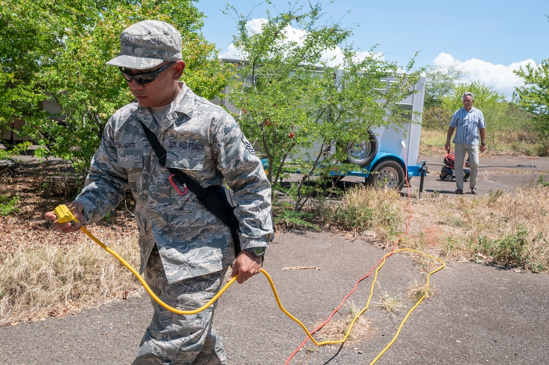 Master Sgt. Bobbyjo Balmonte, 154th Medical Group Detachment 1, Medical Logistics NCO in charge, runs a power cable from a mobile, 5-kW hydrogen fuel cell generator