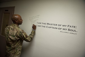 "Chief Master Sgt. of the Air Force Kaleth O. Wright signs an excerpt from the poem 'Invictus' by William Earnest Henley after meeting with master resiliency trainers Oct. 19, 2018, at Nellis Air Force Base, Nevada. As one of Wright's favorite poems, Nellis MRTs asked him to sign it before leaving. He wrote, ""Don't ask for less problems, ask for more skills to deal with them! Thanks for everything you do for our Airmen!"" (U.S. Air Force photo by Airman 1st Class Andrew D. Sarver)"