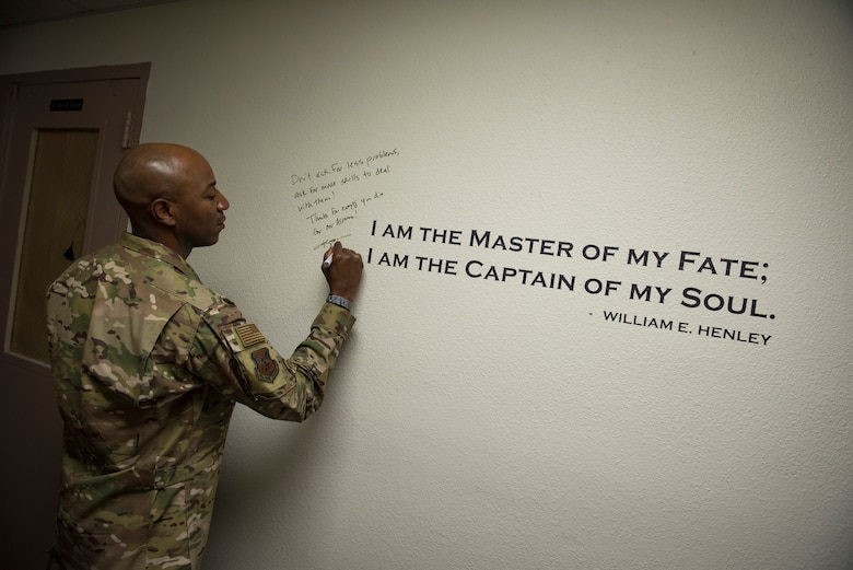 """Chief Master Sgt. of the Air Force Kaleth O. Wright signs an excerpt from the poem 'Invictus' by William Earnest Henley after meeting with master resiliency trainers Oct. 19, 2018, at Nellis Air Force Base, Nevada. As one of Wright's favorite poems, Nellis MRTs asked him to sign it before leaving. He wrote, """"Don't ask for less problems, ask for more skills to deal with them! Thanks for everything you do for our Airmen!"""" (U.S. Air Force photo by Airman 1st Class Andrew D. Sarver)"""