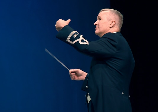 Col. Larry H. Lang, U.S. Air Force Band commander and conductor, leads the band during a performance at Los Alamos High School in Los Alamos, N.M., Oct. 16, 2018. The band aims to inspire patriotism and service as well as honor veterans. (U.S. Air Force photo by Senior Airman Abby L. Richardson)