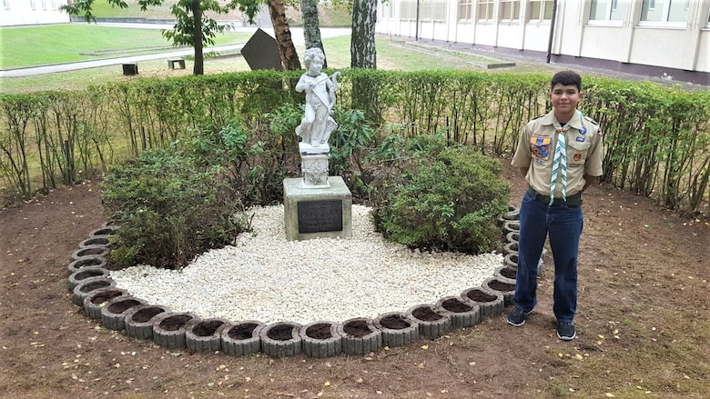 Nathan Perez poses at the newly restored memorial to the late Erick Lynch on October 6, 2018, at what is now Kaiserslautern Middle School.  Lynch was a Kaiserslautern American High School student killed in a hiking accident in 1998.  For his Eagle Scout project, Perez led a small group of his Boy Scout Troop 232 fellows and their parents in the restoration project. The memorial had fallen into neglect over the years. (US Army Reserve Photo by Sgt. 1st Class Juan Perez)