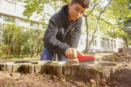 Nathan Perez works to restore a memorial to the late Erick Lynch on October 6, 2018, at what is now Kaiserslautern Middle School. Lynch was a Kaiserslautern American High School student killed in a hiking accident in 1998. For his Eagle Scout project, Perez led a small group of his Boy Scout Troop 232 fellows and their parents in the restoration project. The memorial had fallen into neglect over the years. (U.S. Army Reserve Photo by Sgt. 1st Class John Freese, 7th MSC Public Affairs)
