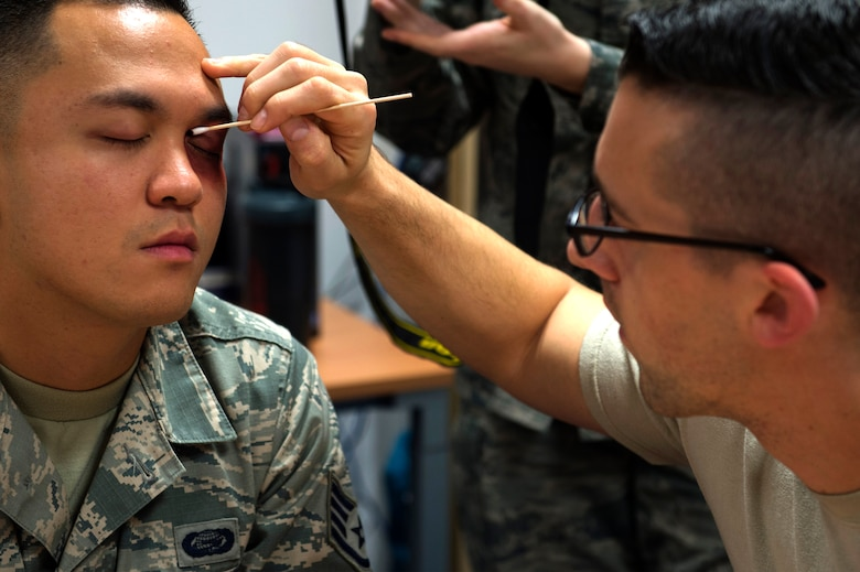 U.S. Air Force Staff Sgt. Jeremy Cole, 86th Medical Operations Squadron mental health technician, applies makeup on U.S. Air Force Staff Sgt. Frank Padeway, 21st Operational Weather Squadron commander support staff noncommissioned officer in charge, on Ramstein Air Base, Germany, Oct. 17, 2018. Padeway, along with five other Airmen assigned across the base, wore makeup for an experiment conducted by the 86th MDOS Family Advocacy Program. Family advocacy wanted to determine how many people would ask the volunteer victims if they needed any assistance. (U.S. Air Force photo by Staff Sgt. Jonathan Bass)