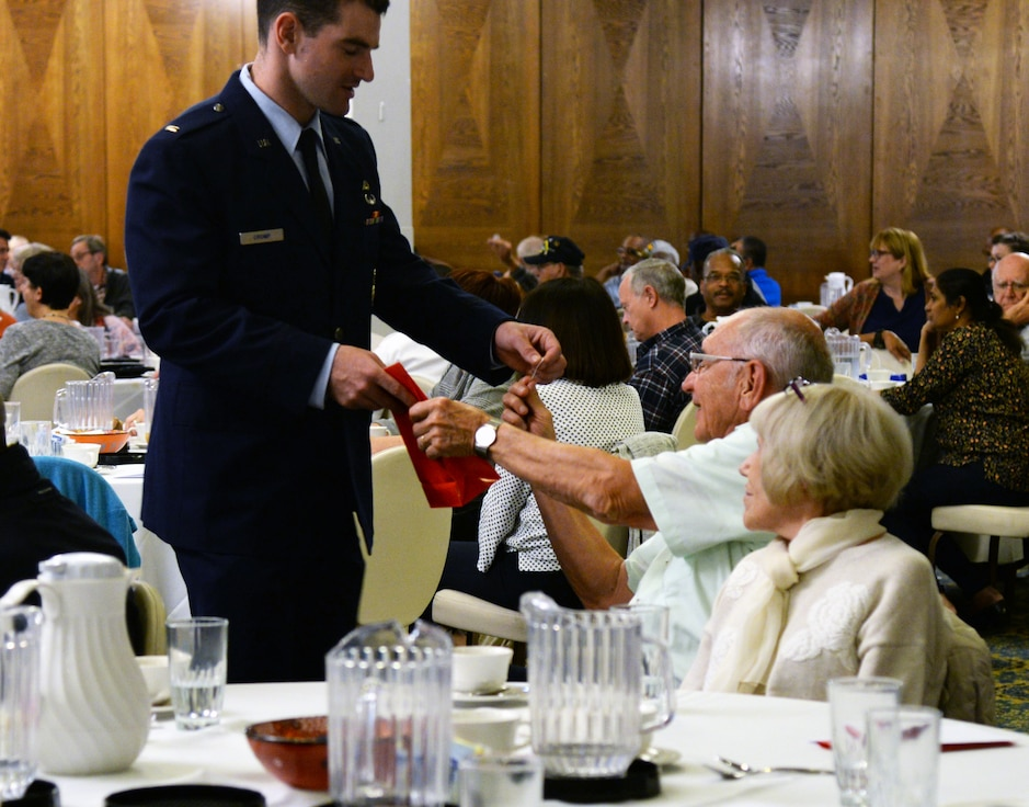 U.S. Air Force 2nd Lt. Stephen Cromp, 569th United States Forces Police Squadron flight commander, gives a prize to a veteran during Retiree Appreciation Day on Ramstein Air Base, Germany, Oct. 18, 2018.