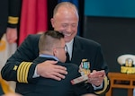 Navy Capt. Brian Ginnane presents his son Seamus with a token of appreciation. Seamus is one of four children that were present for their father's retirement ceremony Oct 12 at the Defense Supply Center Columbus.