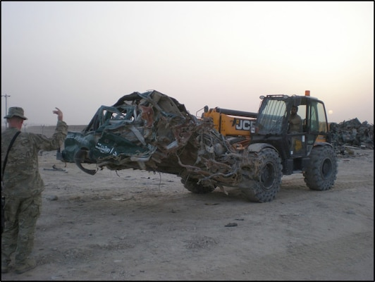 The team uses heavy equipment to moves damaged vehicles to the shearing area.