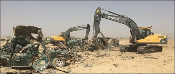 An excavator is used to help crush and stockpile vehicles to be processed as scrap.