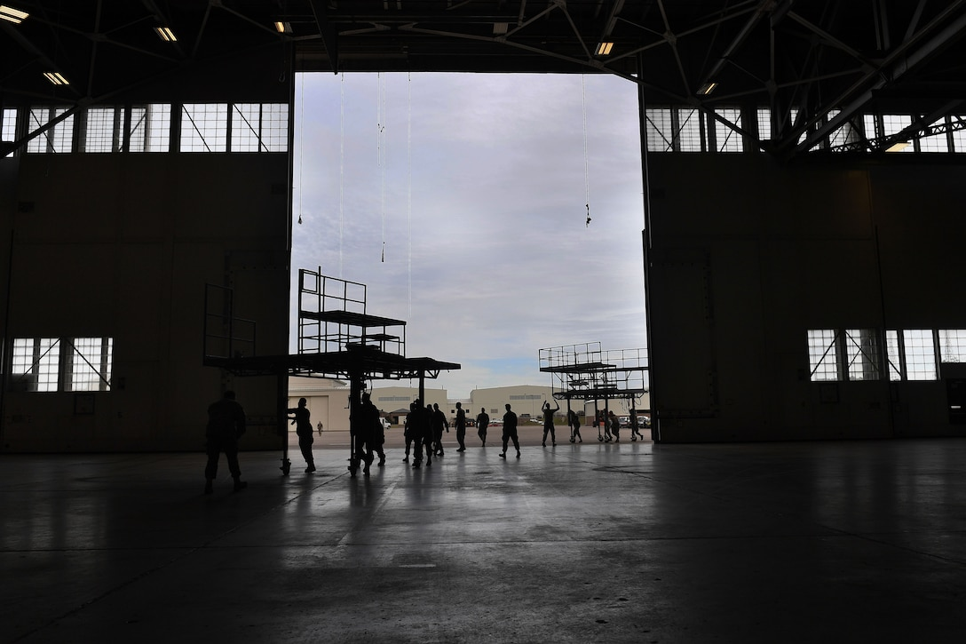 A group of people work in together to move stands through the entryway of a hangar.