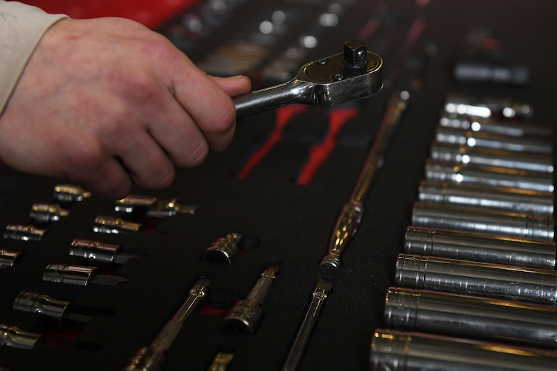 A hand holds a tool over an open toolbox.