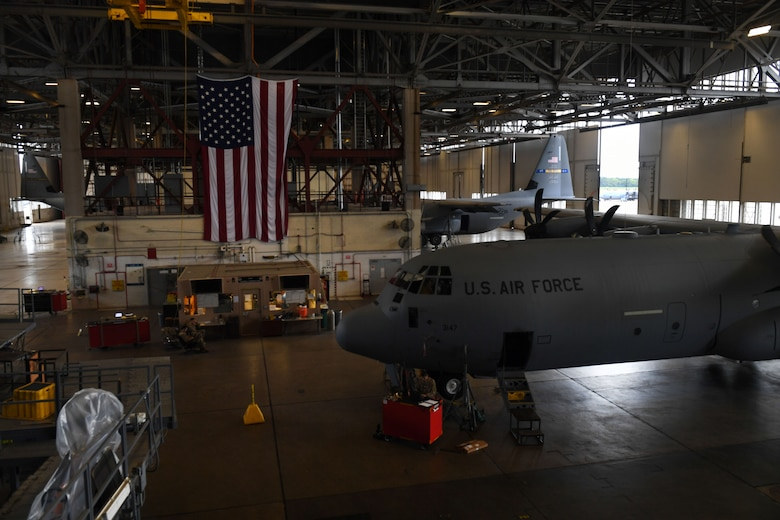 Airmen work in a large, open hangar.