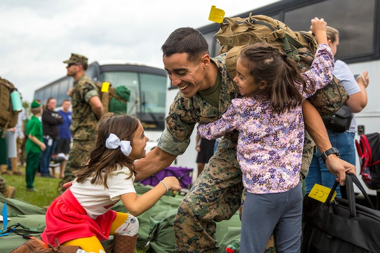 One little girl hugs a smiling Marine as he reaches down to hug another one.