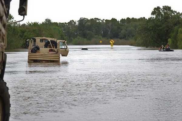 Texas National Guardsmen support vehicles approach a flooded roadway near Huntsville, Texas, Oct. 18, 2018.  Texas Guardsmen worked alongside emergency first responders to help Texans in need during severe flooding.