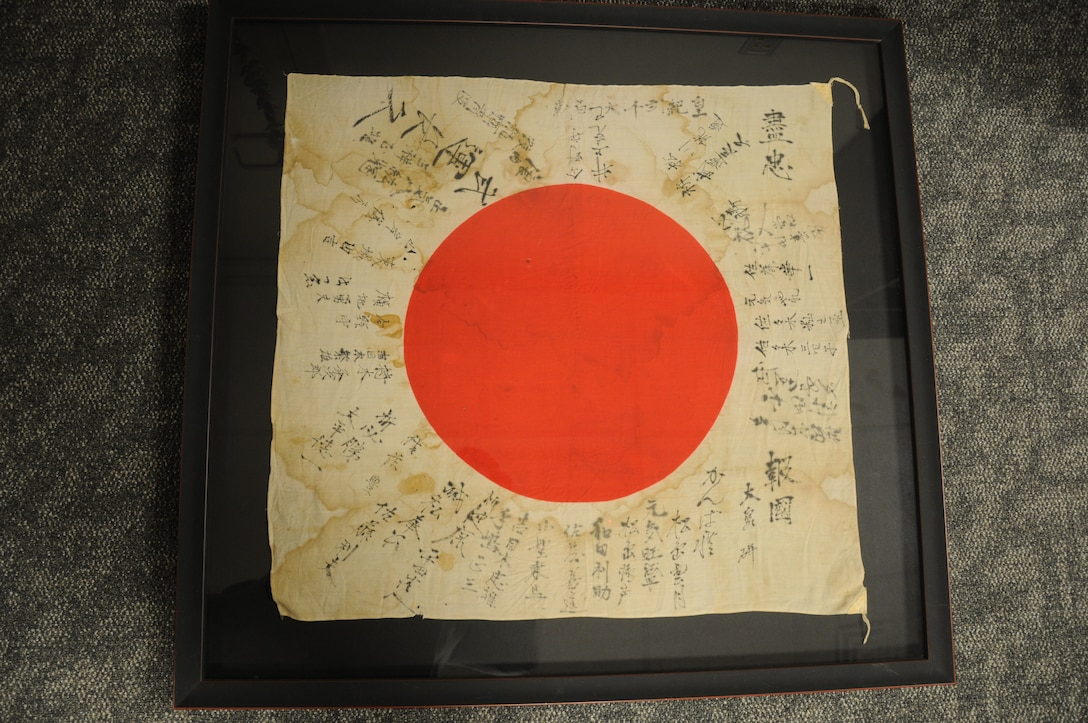 Fitted in a frame for preservation, Dr. Jordan is both haunted and intrigued by the tattered Japanese war flag.