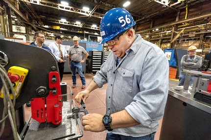 Jeff Pugh, a pipefitter, uses a new 3D-printed alignment tool to help punch holes in an iron pipe hanger.