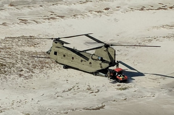 A New York Army National Guard CH-47 Chinook helicopter transports search and rescue personnel and their all-terrain vehicles to St. Teresa, along the shoreline of the Florida panhandle, Oct. 12, 2018. The New York Army National Guard Soldiers deployed two Chinooks and two UH-60 Black Hawk helicopters along with 25 crew members to Tallahassee, Florida, to assist with response and recovery efforts for the Florida National Guard following the impact of Hurricane Michael.