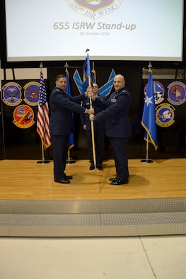 Col. John D. McKaye, 655th Intelligence, Surveillance, and Reconnaissance Wing provisional commander, passes the guidon to Col. Joshua C. Redden, 755th Intelligence, Surveillance, and Reconnaissance Group commander, during the 755th ISRG activation ceremony here Oct. 20, 2018. The 655th ISRW encompasses two groups, the 655th ISRG, located here, and the 755th ISRG, located at Joint Base Langley-Eustis, Virginia, and 14 squadrons over seven operating locations engaged in 10 distinct mission sets. (U.S. Air Force photo/Senior Airman Holly Ardern)