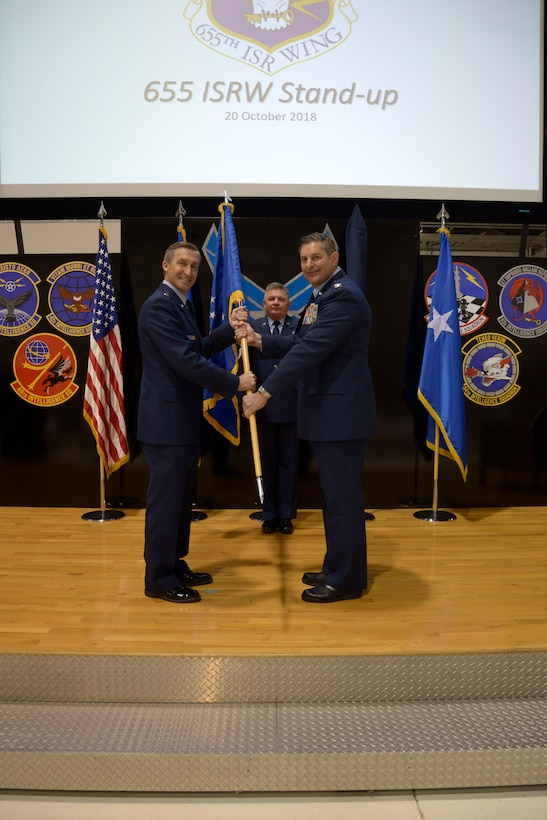 Maj. Gen. Ronald B. Miller, 10th Air Force commander, passes the guidon to Col. John D. McKaye, 655th Intelligence, Surveillance, and Reconnaissance Wing provisional commander, during the 655th ISRW Stand-up ceremony here Oct. 20, 2018. The 655th ISRW encompasses two groups, the 655th ISRG, located here, and the 755th ISRG, located at Joint Base Langley-Eustis, Virginia, and 14 squadrons over seven operating locations engaged in 10 distinct mission sets. (U.S. Air Force photo/Senior Airman Holly Ardern)
