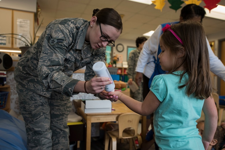 Airman 1st Class Samantha Downey, 436th Aerospace Medicine Squadron public health technician, puts a germ-simulating lotion on the hands of Alessandra Lowry, a student at the Child Development Center, Oct. 16, 2018, during a hand-washing demonstration at the CDC on Dover Air Force Base, Del. The lotion acts as germs on the children's hands and even after washing some residue may still show up under a black light. (U.S. Air Force photo by Airman 1st Class Zoe M. Wockenfuss)