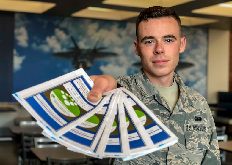 U.S. Air Force Airman 1st Class Graham Cunliffe-Owen, 633rd Air Base Wing cybersecurity technician, hands out pamphlets promoting good cybersecurity techniques for National Cyber Security Awareness month at the Joint Base Langley-Eustis, Virginia, Oct. 10, 2018.