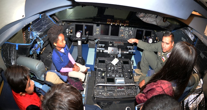 Maj. Brian L. Biggerstaff, 68th Airlift Squadron pilot, quizzes third-grade students from Meredith Baskin Elementary about aircraft controls on the flight deck of a C-5M Super Galaxy at Joint Base San Antonio-Lackland Oct. 19, 2018.