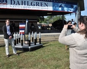 IMAGE: DAHLGREN, Va. (Oct. 19, 2018) – Dahlgren personnel take pictures with the time capsule at the Naval Surface Warfare Center Dahlgren Division (NSWCDD) centennial grand finale. As participants celebrated Dahlgren's impact upon the Navy and nation, the time capsule – ten 105 millimeter shells surrounding a 16-inch shell –  was unveiled and all in attendance had the opportunity to write notes and share their thoughts with future generations. Dahlgren personnel can write notes to be placed inside the capsule until the end of 2018 when it will be sealed and opened on Oct. 16, 2068 at the command's 150th anniversary.