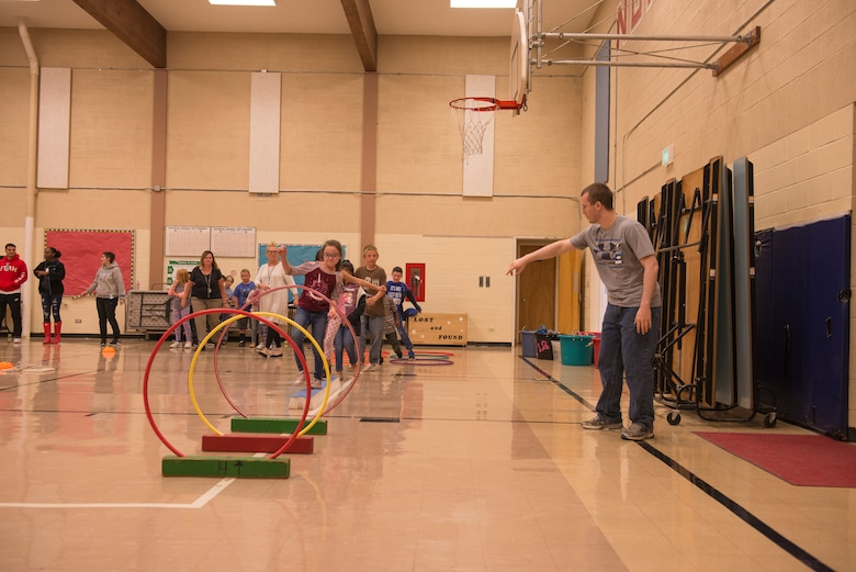 """Airmen from the 366th Fighter Wing help students complete an obstacle course at North Elementary School, in Mountain Home, Idaho, October 4, 2018. North Elementary hosted their annual """"Move-A-Thon"""" as a fundraiser for the students to go on field trips. (U.S. Air Force photo by Senior Airman Tyrell Hall)"""