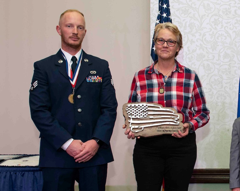 Senior Airman Payton Long, 375th Civil Engineer Squadron structural apprentice, presents Cathy Berlin-Obregon a plaque honoring her sister, Air Force Academy instructor Maj. Phillis Pelky, at the Class 18-G Airman Leadership School graduation. Pelky was killed in a 2015 helicopter crash in Afghanistan, which also took the life of Kuhse. (U.S. Air Force photo by Senior Airman Tara Stetler)