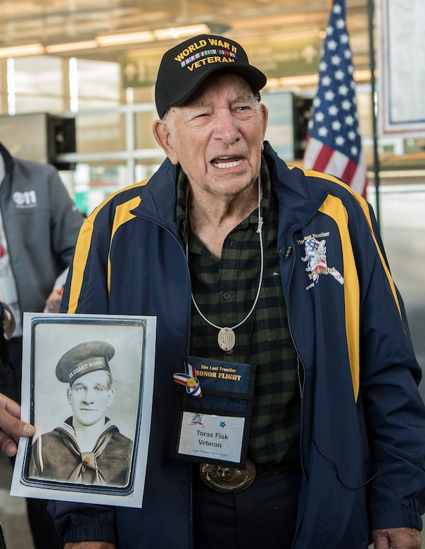 Toras Fisk, a World War II veteran, stands by an official military photo of himself, at Ted Stevens International Airport, before leaving for Washington, D.C., with the Last Frontier Honor Flight, Alaska, Oct. 16, 2018. The program offers veterans the opportunity to visit monuments erected in their honor such as the National World War II Memorial, the Korean War Veterans Memorial and the Vietnam Veterans Memorial.